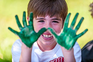 young boy with paint all over his hands