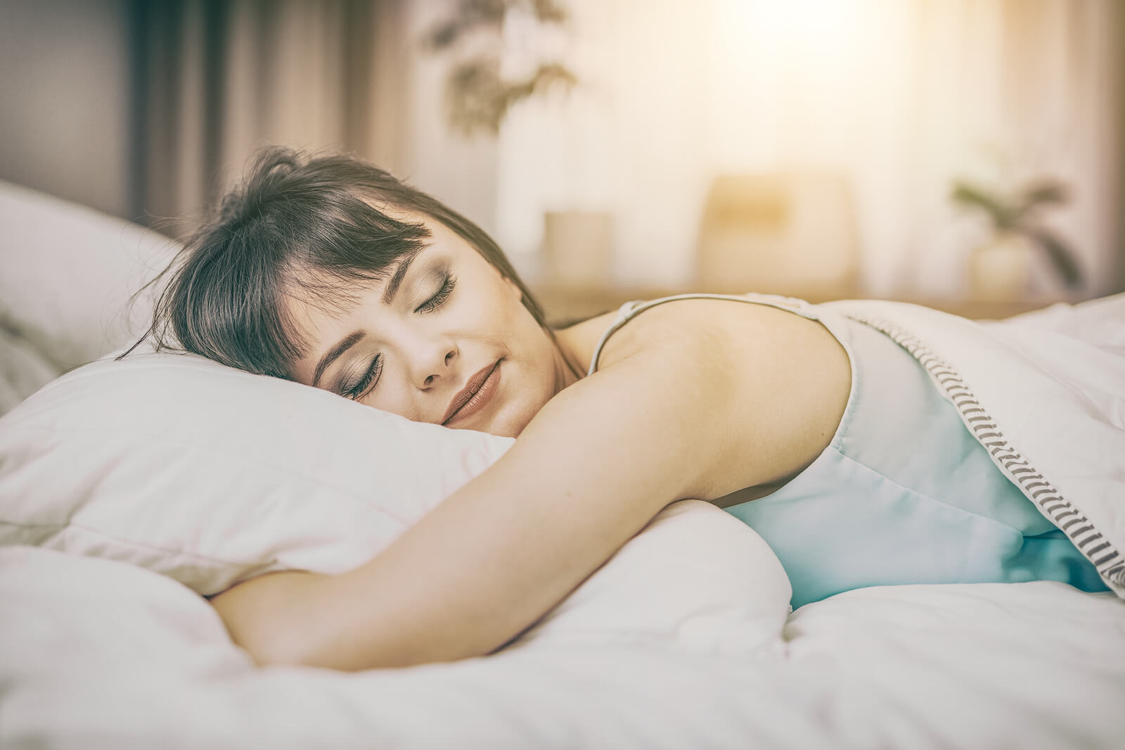 Beautiful young woman sleeping on a bed in the bedroom in a peaceful sleep