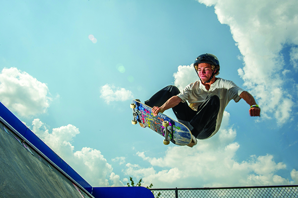 Boy catching air on skateboard in sports park