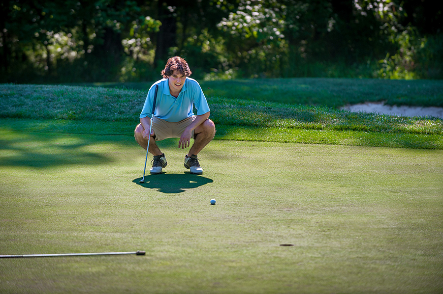 man stooping down on golf course